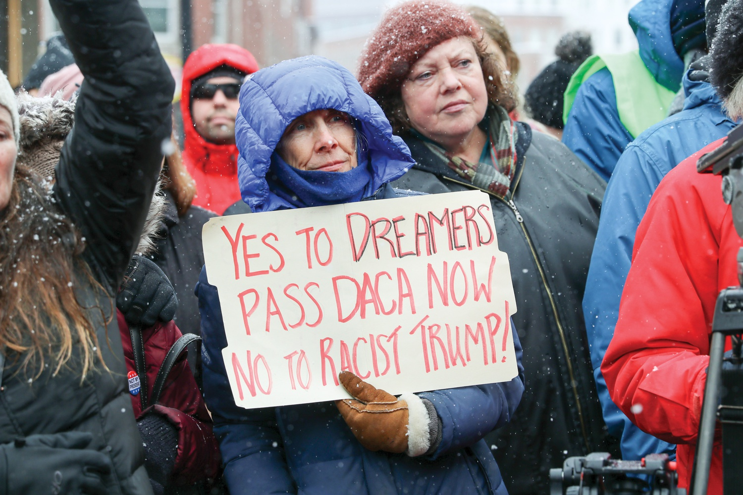 A woman holds a sign supporting Deferred Action for Childhood Arrivals recipients at a Monday protest, criticizing President Donald Trump's declaration of a national emergency to build a border wall.