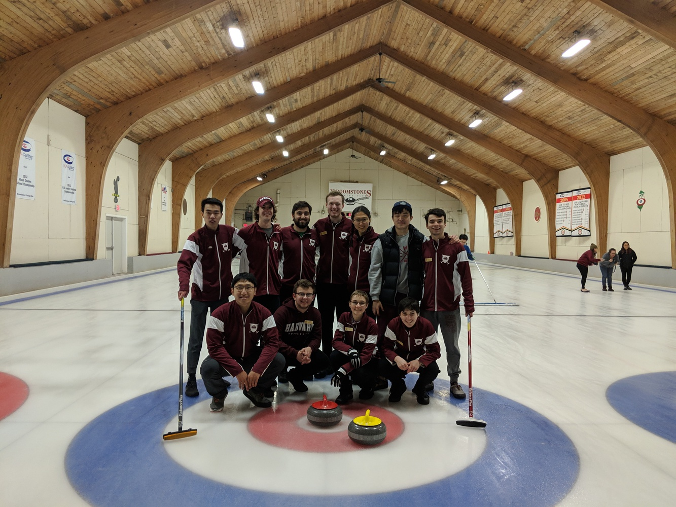 The Harvard Curling Club poses holding their equipment: stones and brooms used during competition.