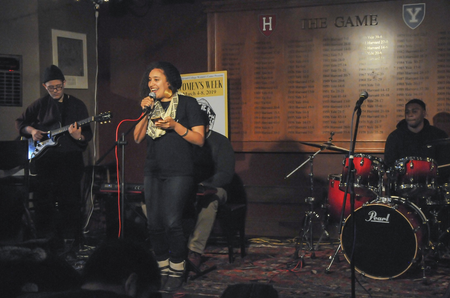 Azmera Hammouri-Davis sings and Alexa K. Mayer plays at Sing It, Sister!, a Women's Week open mic event in the Cambridge Queen's Head pub Wednesday night.