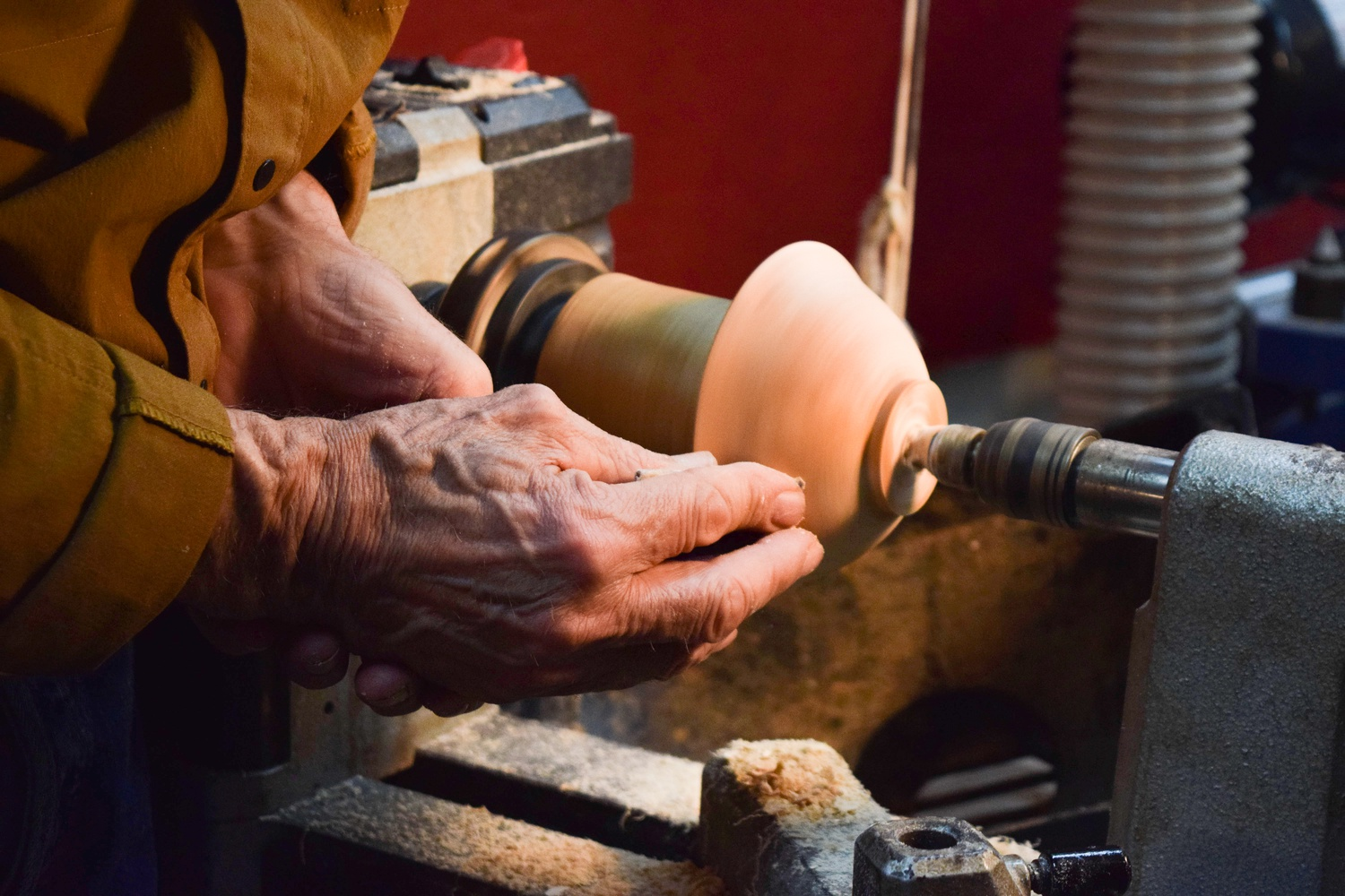 Alan Hark uses his hands to sand the outside of one of his students' wooden bowls, made of Black Cherry, as it spins on the lathe.