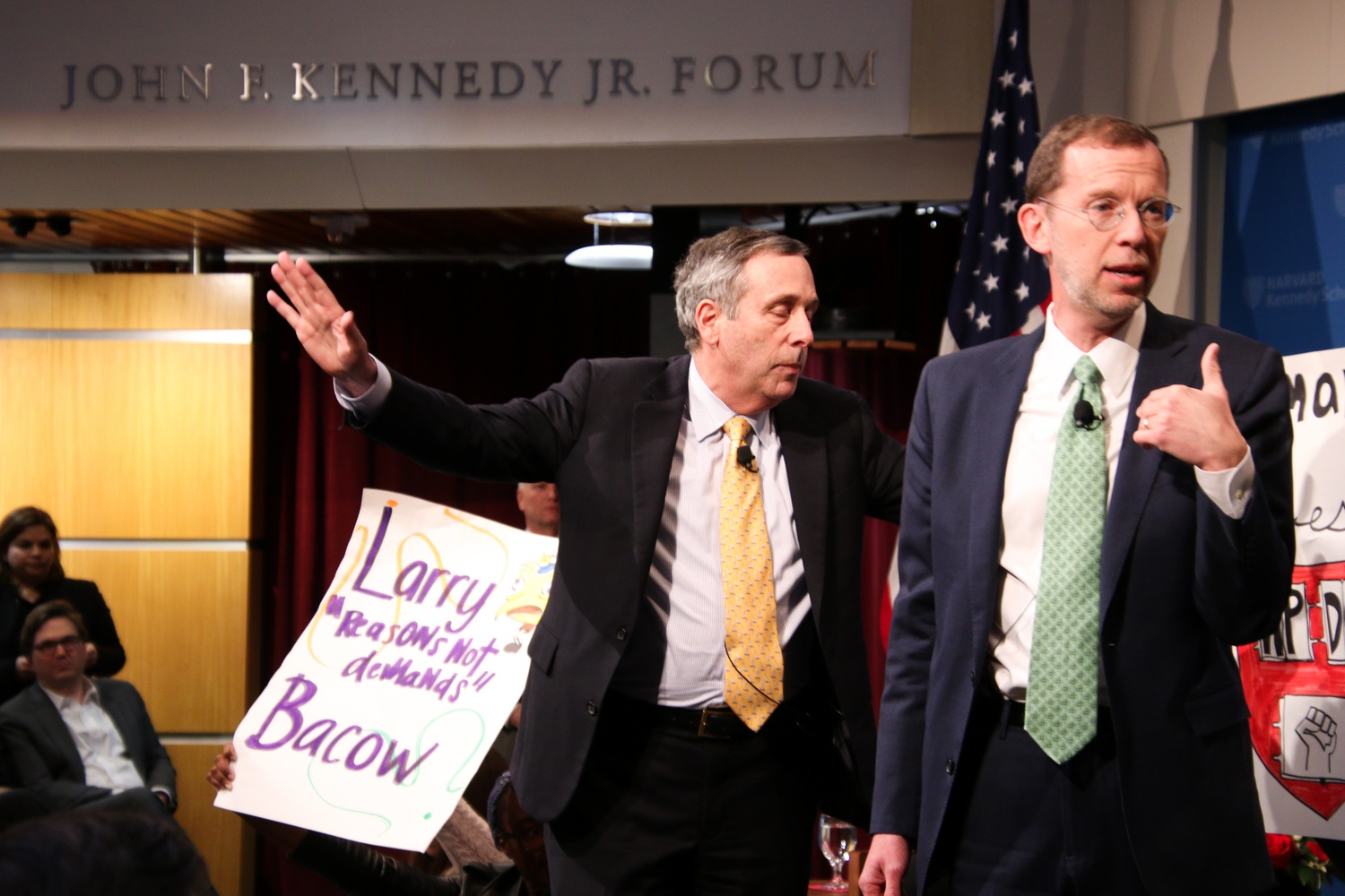 University President Lawrence S. Bacow attempts to quiet protestors before exiting the John F. Kennedy Jr. Forum.