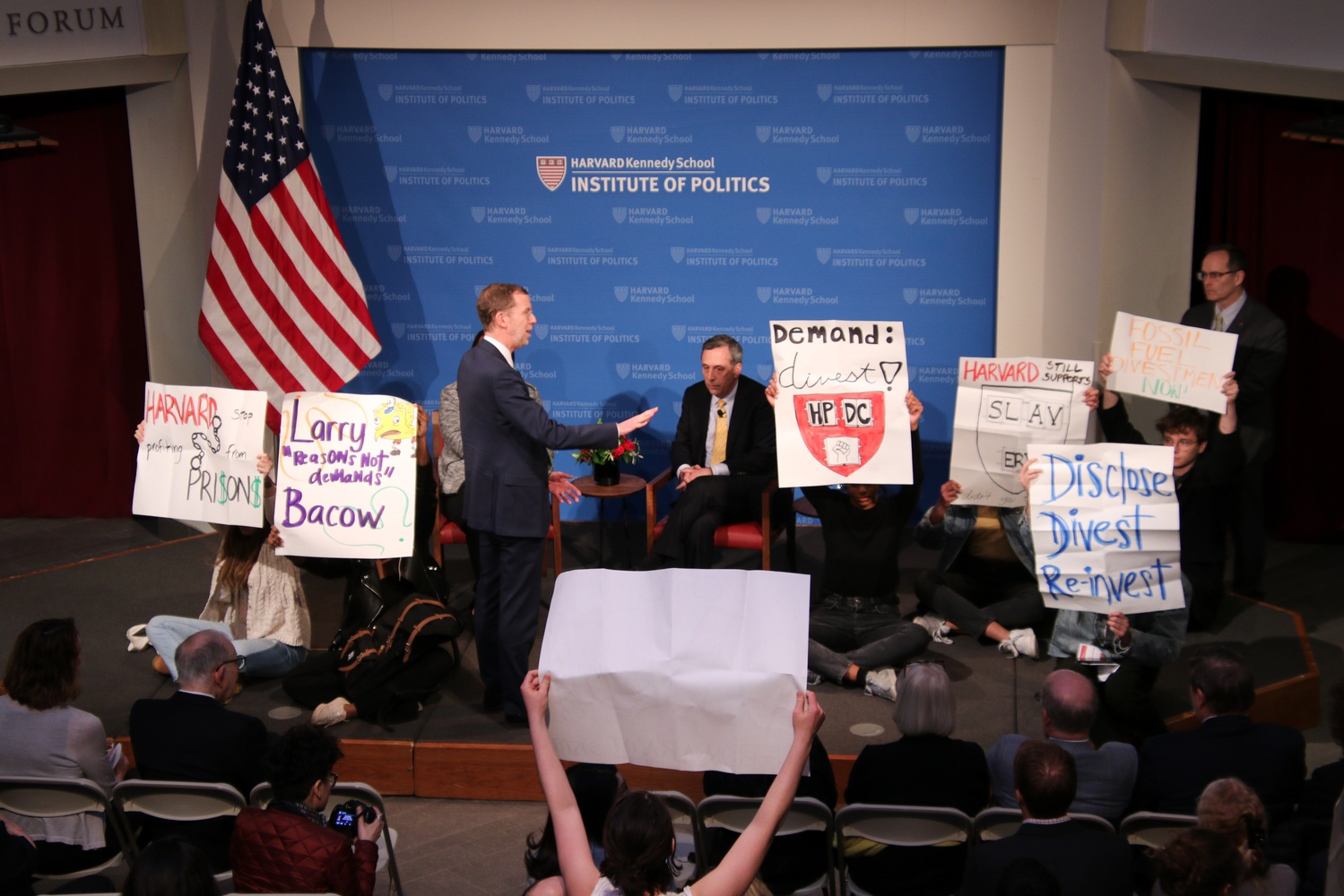 Protestors from Divest Harvard and the Harvard Prison Divestment Campaign interrupt an Institute of Politics event featuring University President Lawrence S. Bacow Thursday evening.