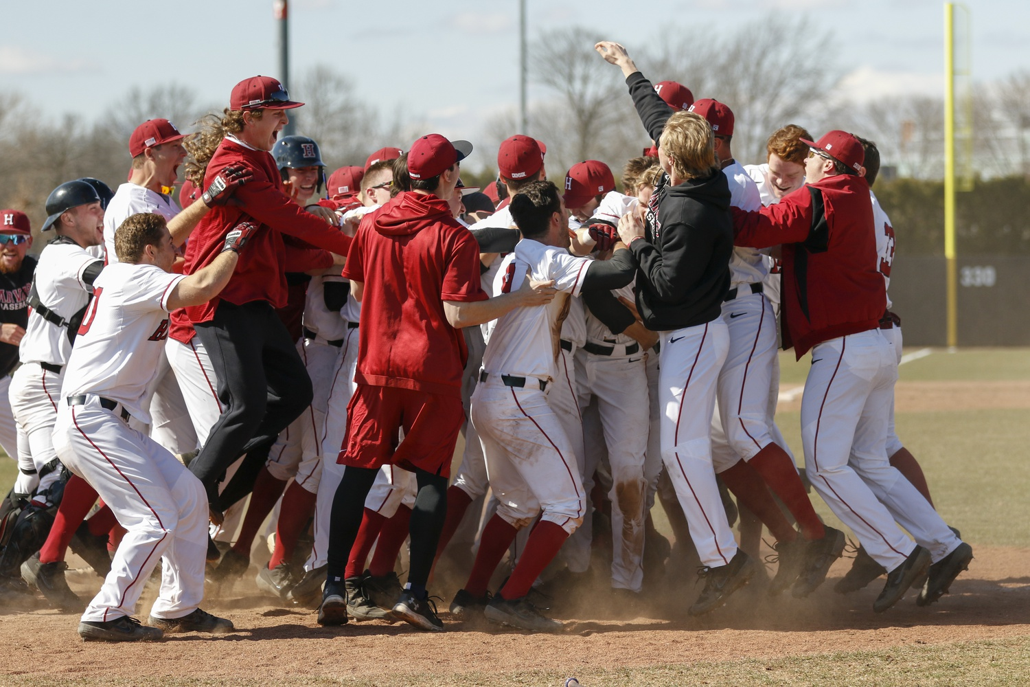 The team celebrates after a nine-run, ninth inning to take the first game against Yale.