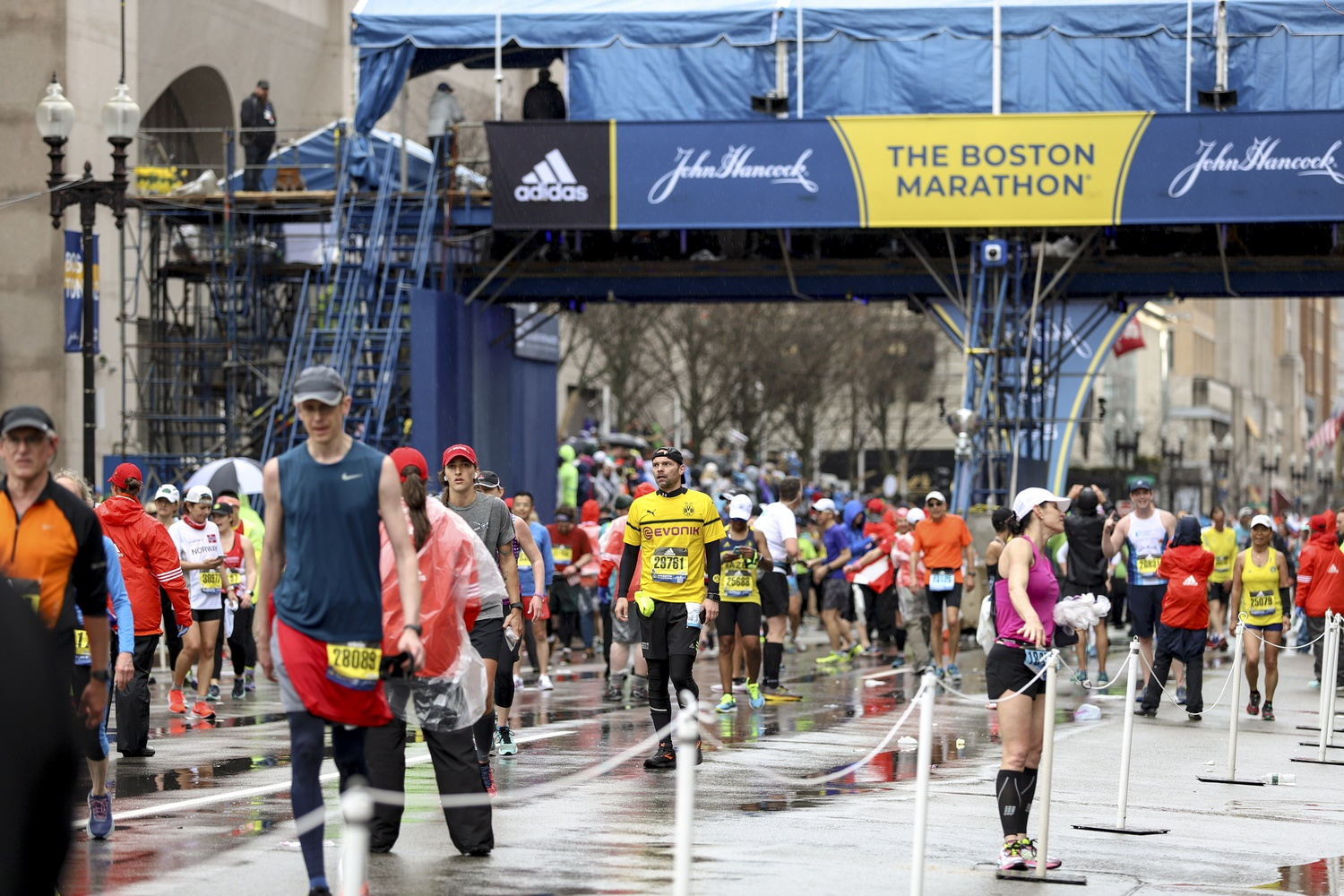 After finishing the race in the rain, Boston Marathon runners leave the course on Monday afternoon.