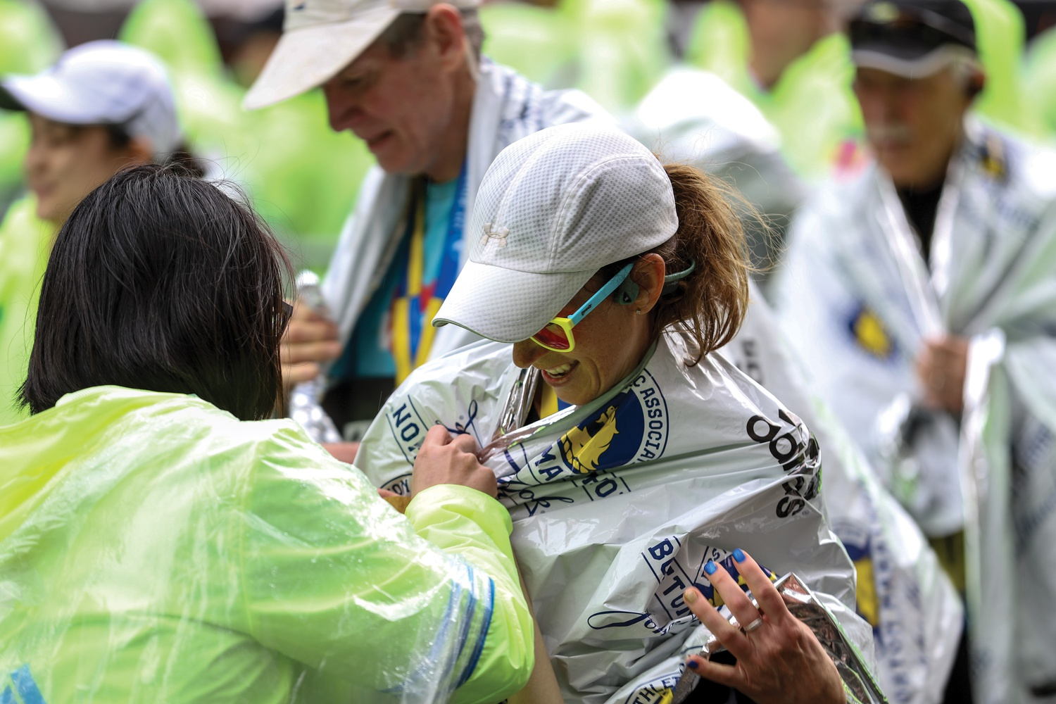 A marathon participant has a mylar blanket wrapped around her after concluding the race.
