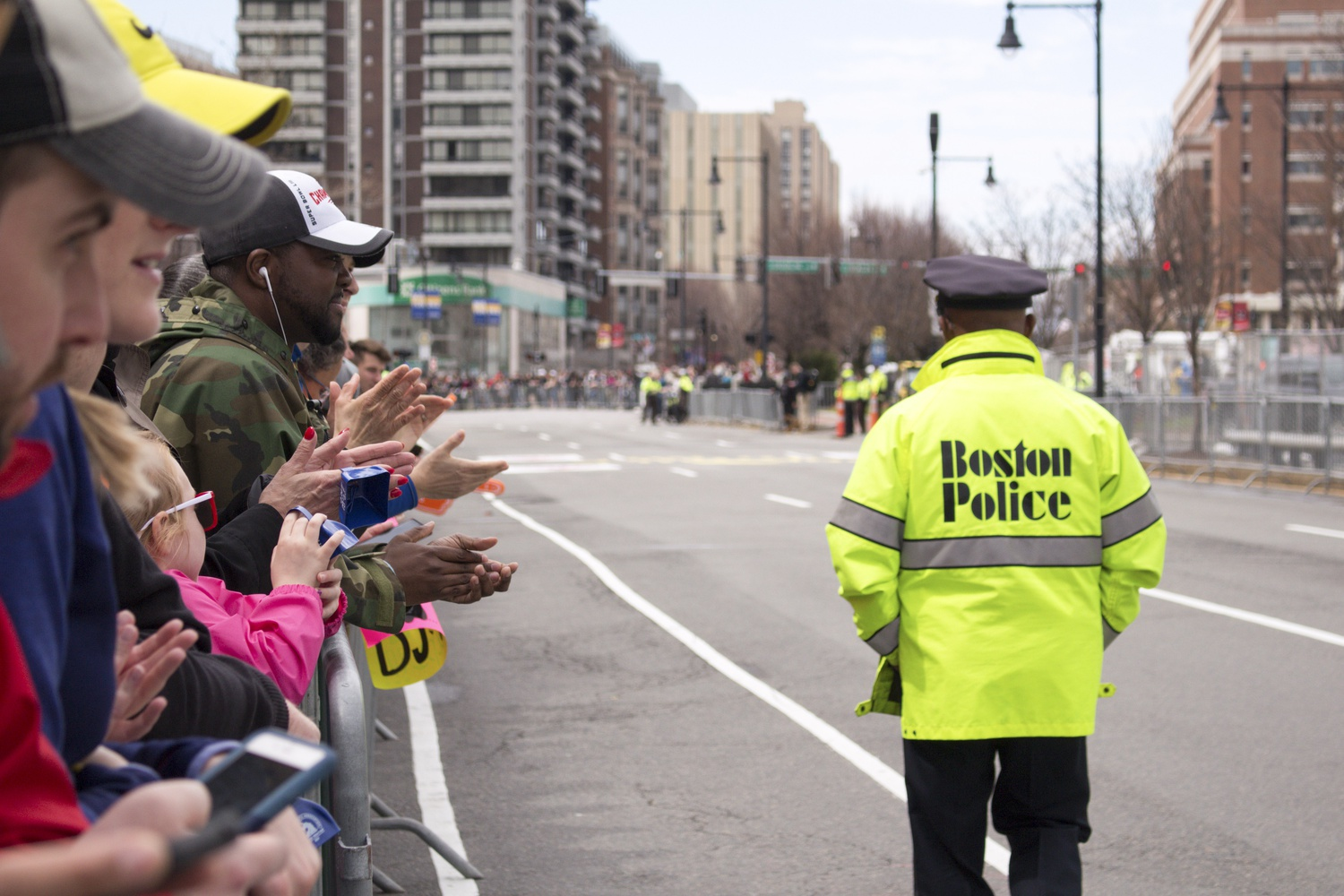 Crowds cheer on Boston Marathon runners as the Boston Police ensure the safety of the participants and onlookers.