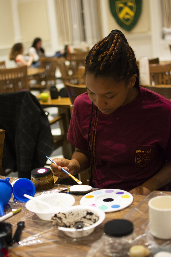 Delanya M. Storey '21 decorates a stone after mixing a custom body scrub at the OSAPR study break held in Leverett House.