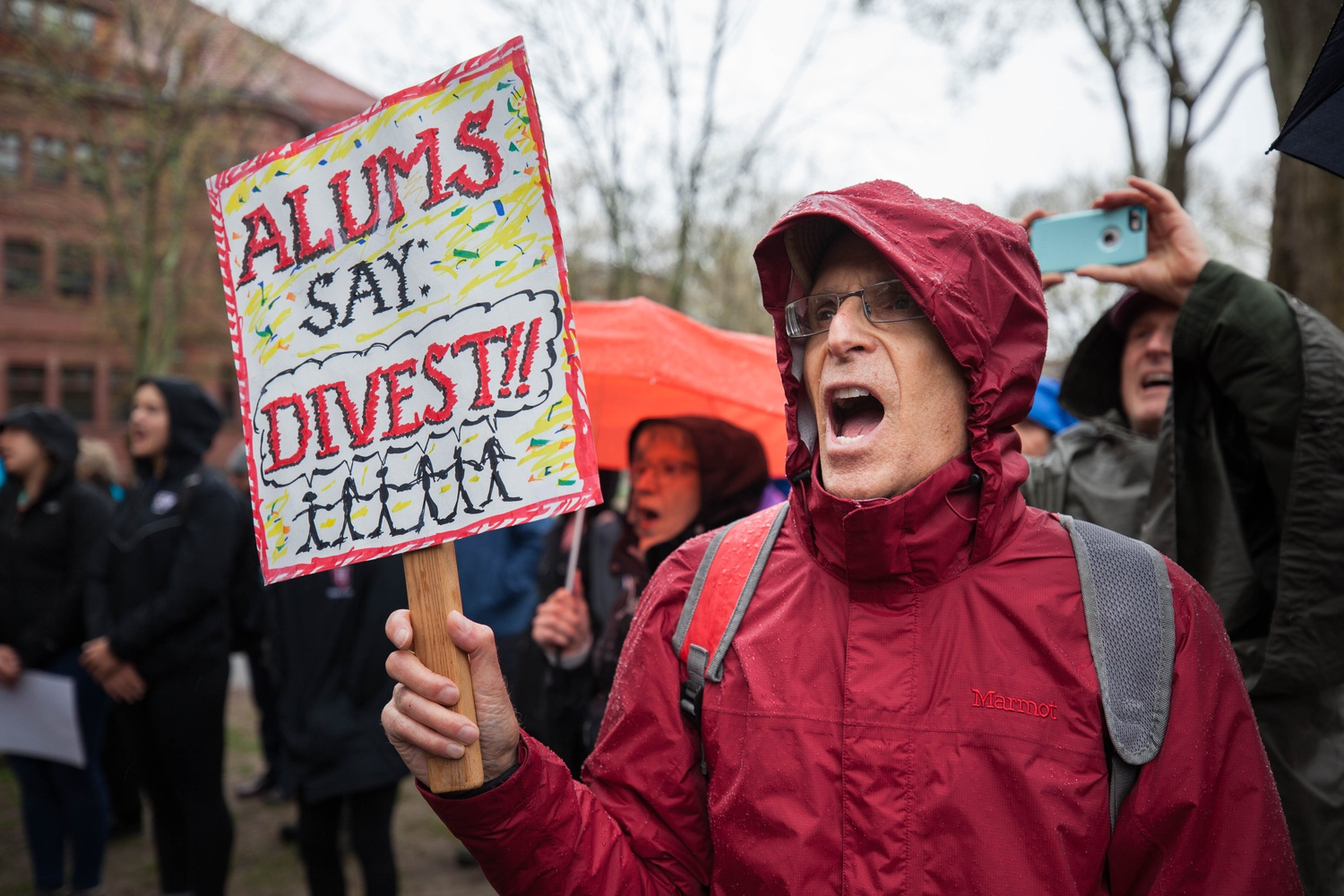 A Harvard alum holds a sign proclaiming his support for Divest Harvard, an undergraduate-led effort to push the University to divest funds from fossil fuels.