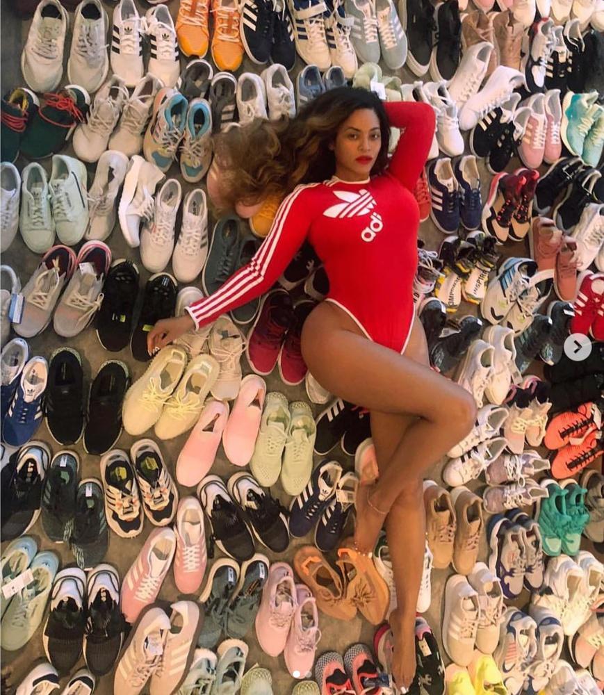Beyoncé reclines on a sea of shoes.