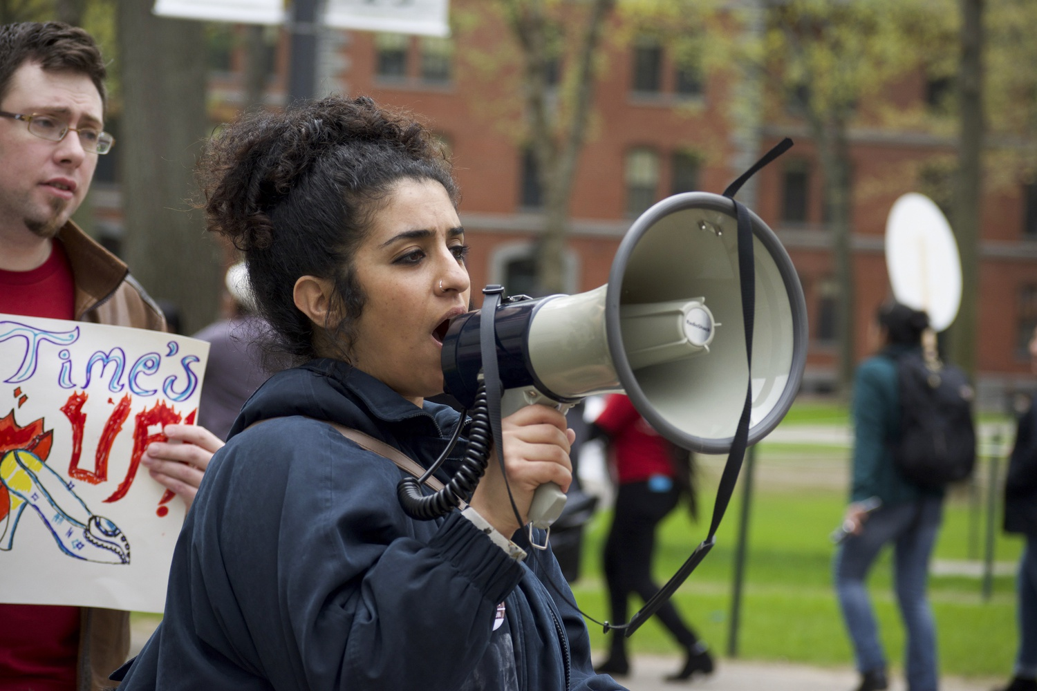 A protester speaks to the crowd as she leads the crowd on their march in Harvard Yard. Protestors sang organized chants during the march.