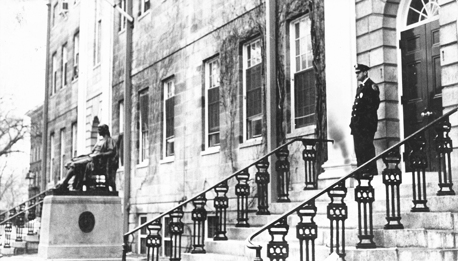 A guard stands watch at one of University Hall's entrances in 1969.