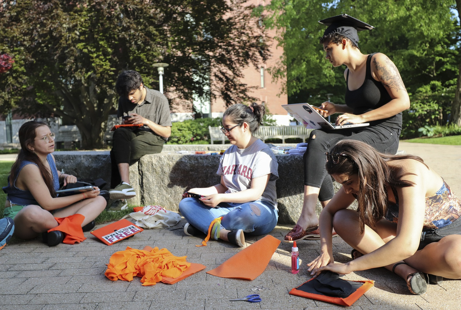 Members of Divest Harvard and the Harvard Prison Divestment Campaign decorate their graduation caps with orange cloth and felt outside the Casper Student Center Monday evening. Orange is the color of the fossil fuel divestment movement.