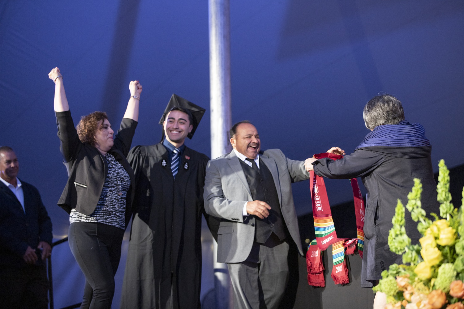 Family members draped graduating students with Latinx stoles as they walked on stage. The Latinx Commencement took place Tuesday evening at Radcliffe Yard.