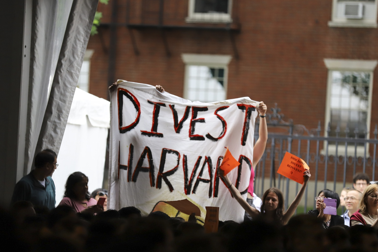 Members of Divest Harvard raised a banner calling on Harvard to divest its endowment from fossil fuel industries during University President Lawrence S. Bacow's Convocation address Monday.