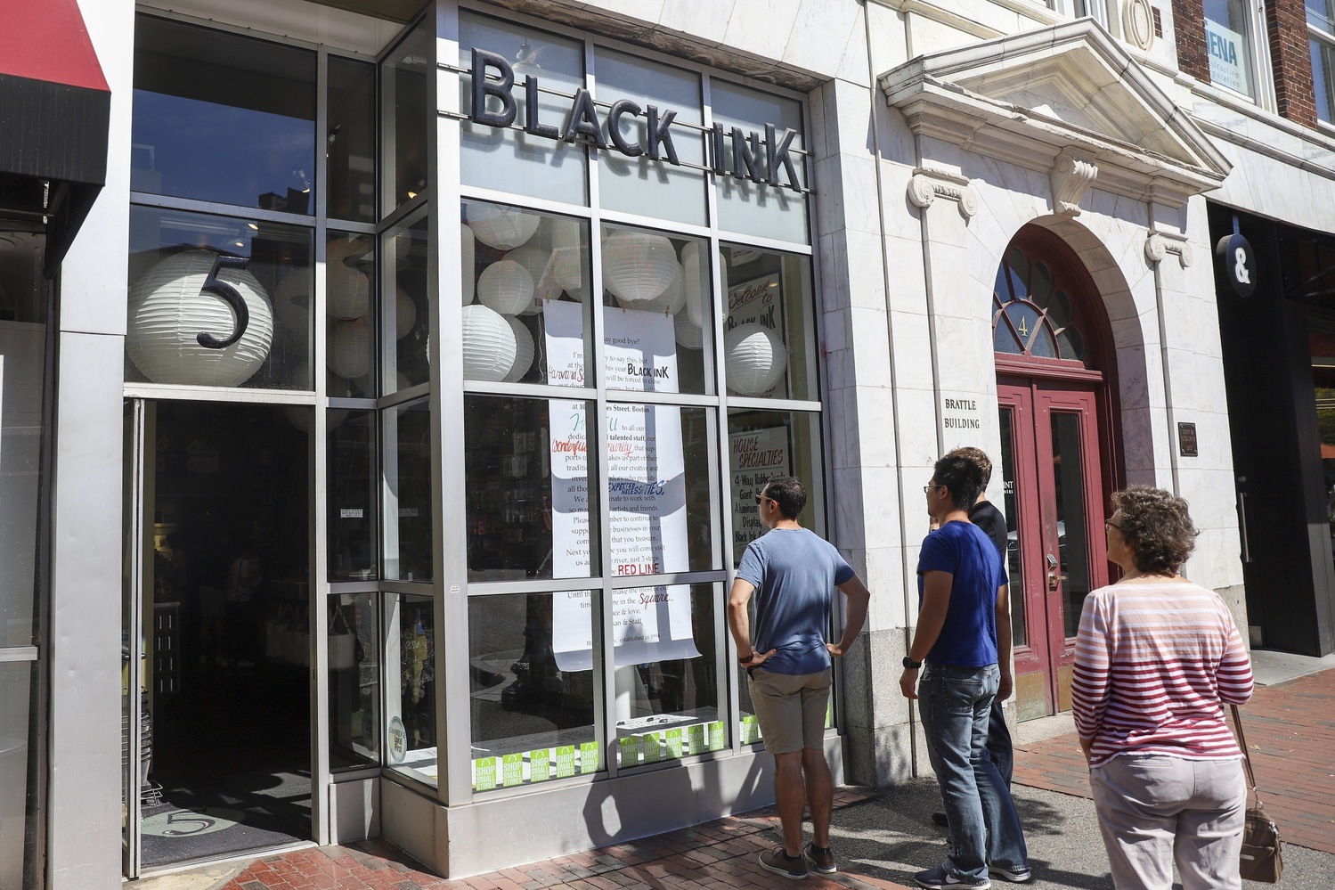 Harvard Square visitors stop to read the sign in front of Black Ink, which is shutting down amidst rising rent.
