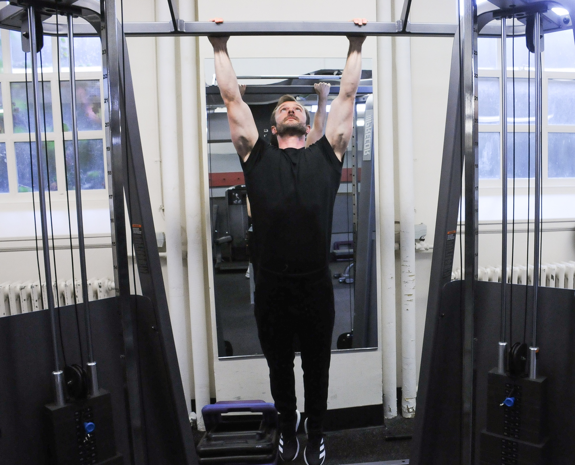 Harvard lecturer Adam E. A. Sandel '08 does pull-ups in the Malkin Athletic Center.