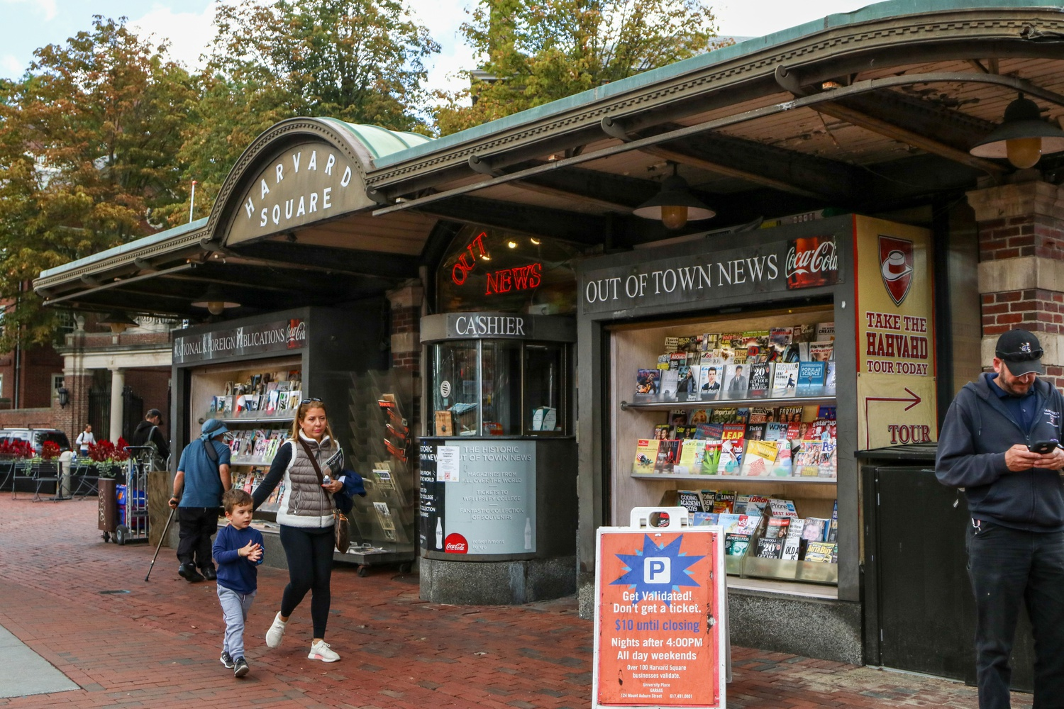 Visitors to Harvard Square walk past Out of Town News in Harvard Square Wednesday afternoon. The newsstand is scheduled to close at the end of October.