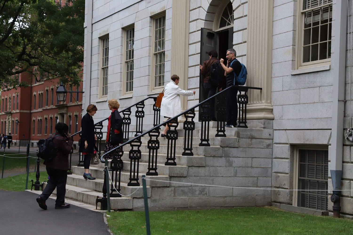 Professors and administrators walk into University Hall ahead of a monthly faculty meeting.