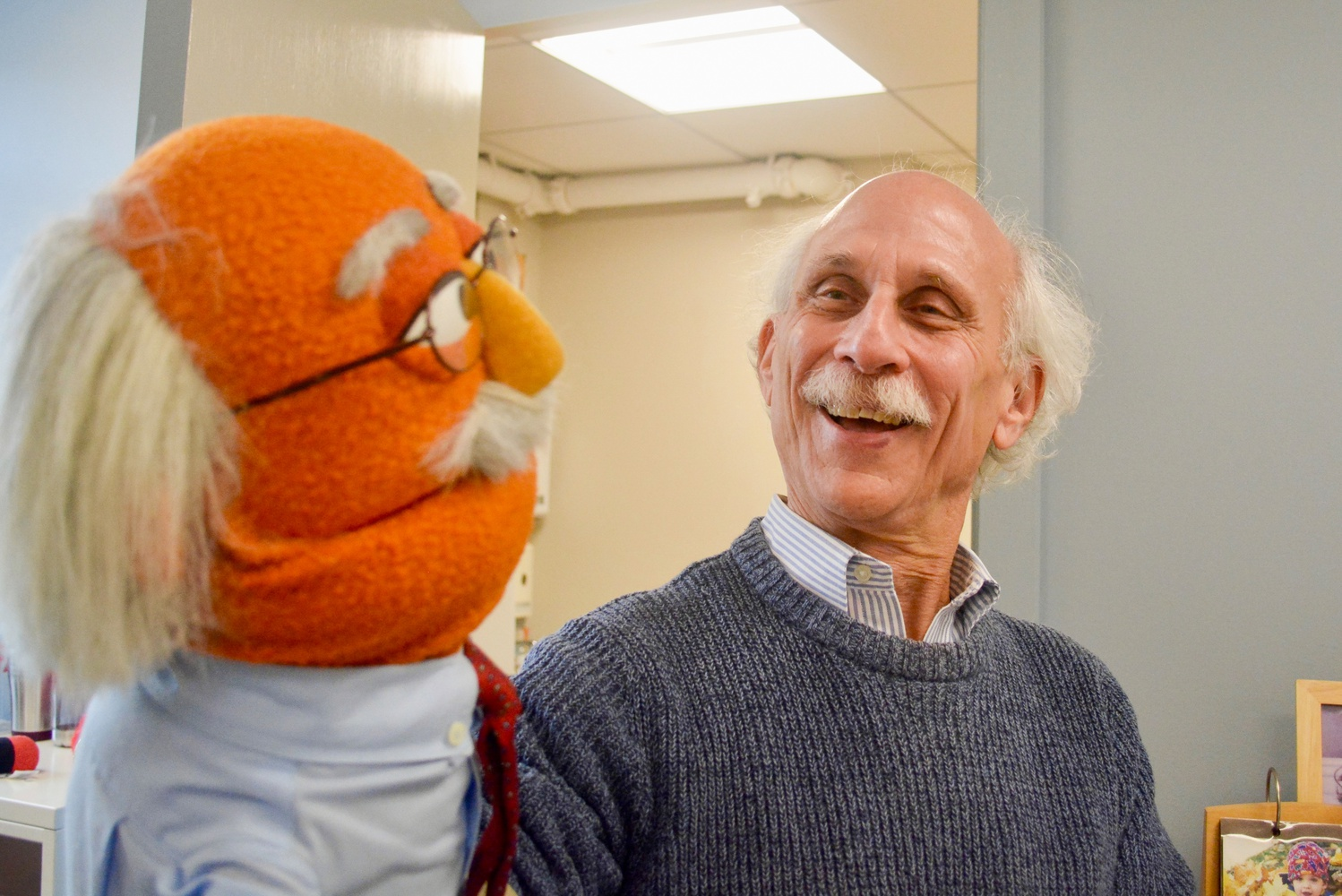 Joseph Blatt, the faculty director of the Master's Program in Technology, Innovation and Education, laughs with his muppet in his office Friday afternoon.