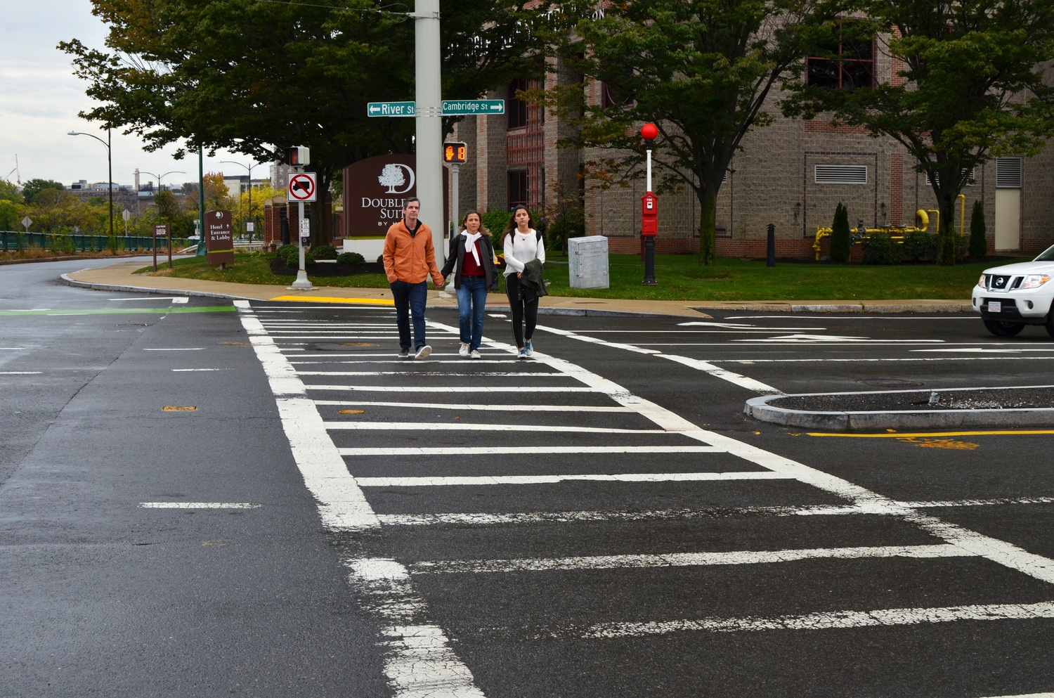 Pedestrians cross Soldiers' Field Road across the Charles River.