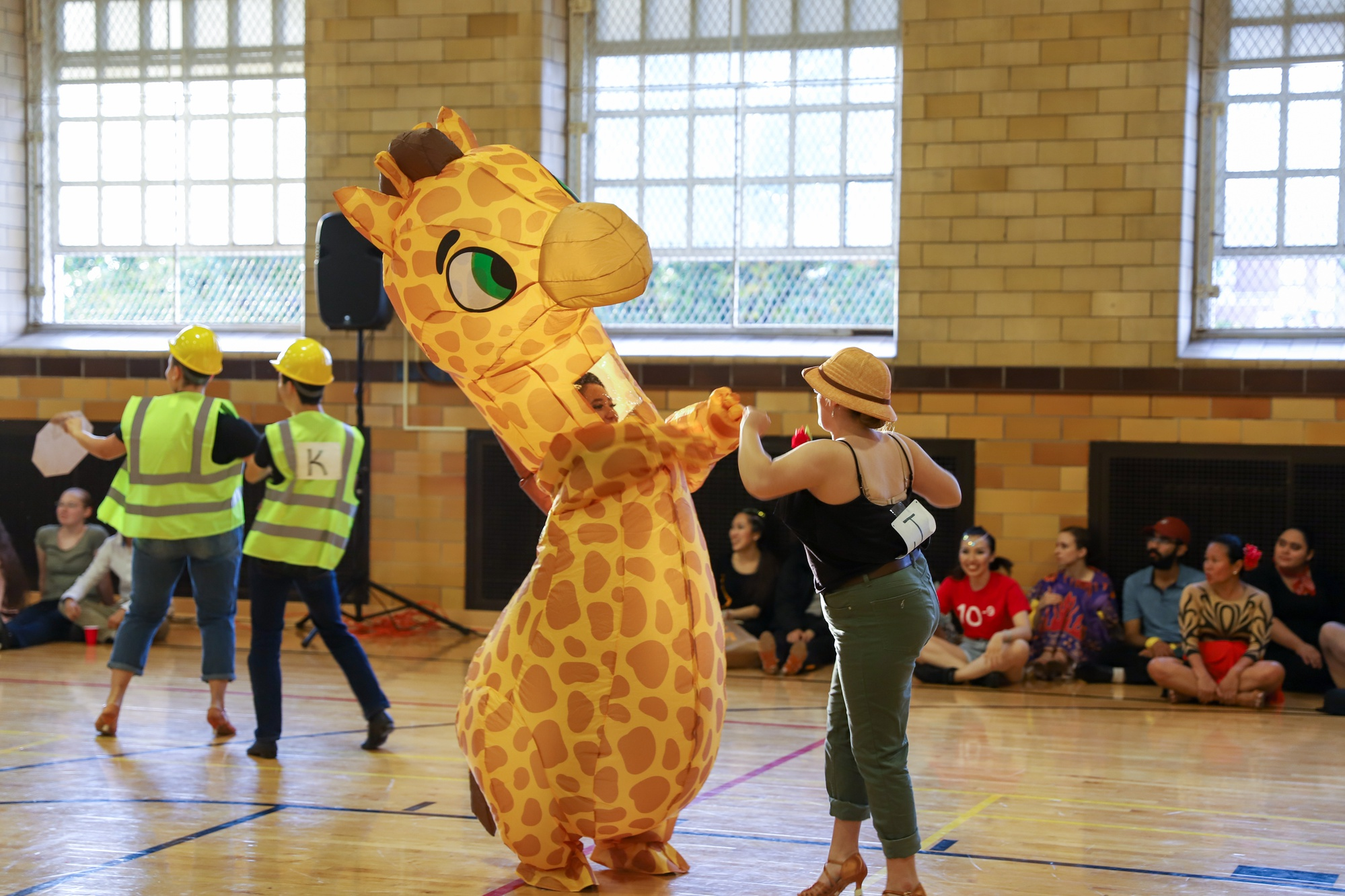Several dancers at the Harvard Beginners ballroom competition dressed in zany costumes, including inflatable dinosaur and giraffe costumes.