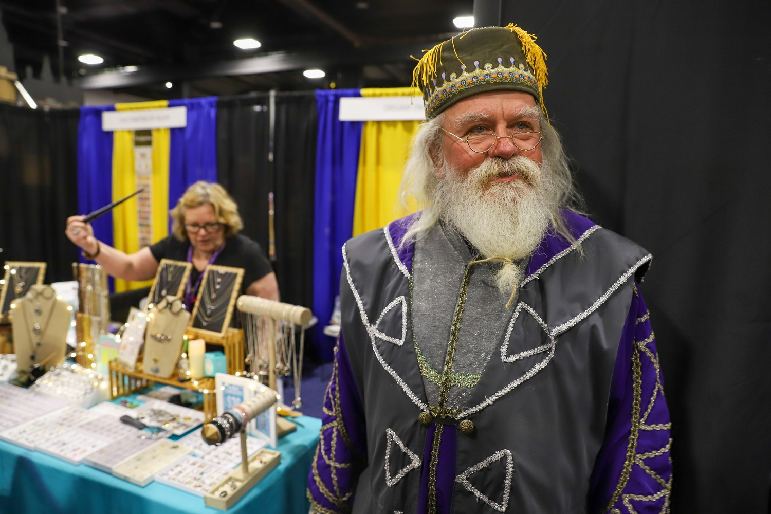 Dave P. Maccawley, cosplaying as Albus Dumbledore, attends his first LeakyCon with his wife Laura, selling jewelry and small trinkets.