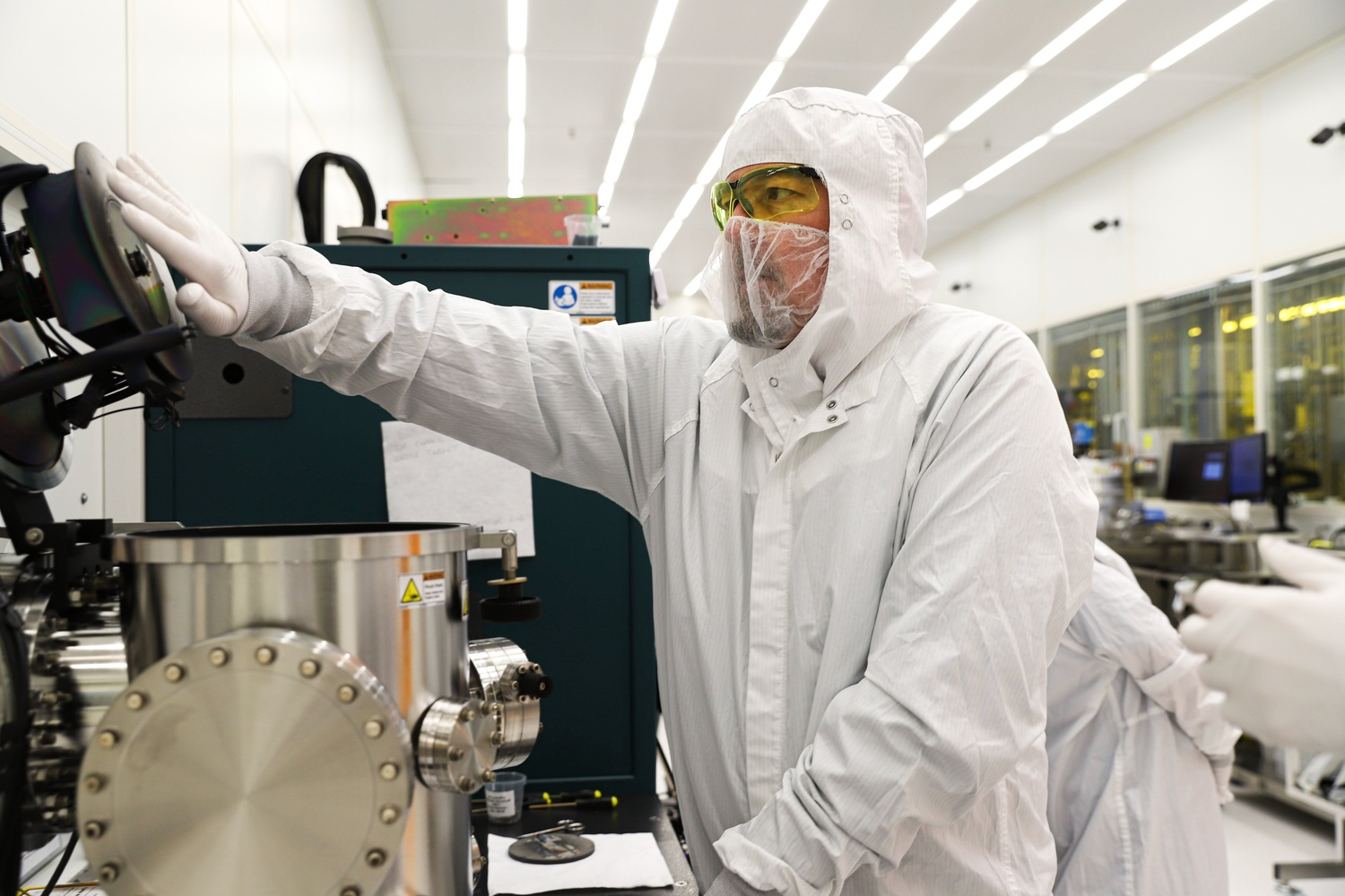 Ed Macomber opens a chamber of a sputter deposition system in Harvard's Center for Nanoscale Systems cleanroom. Macomber is an engineer in the CNS Nanofabrication Group.