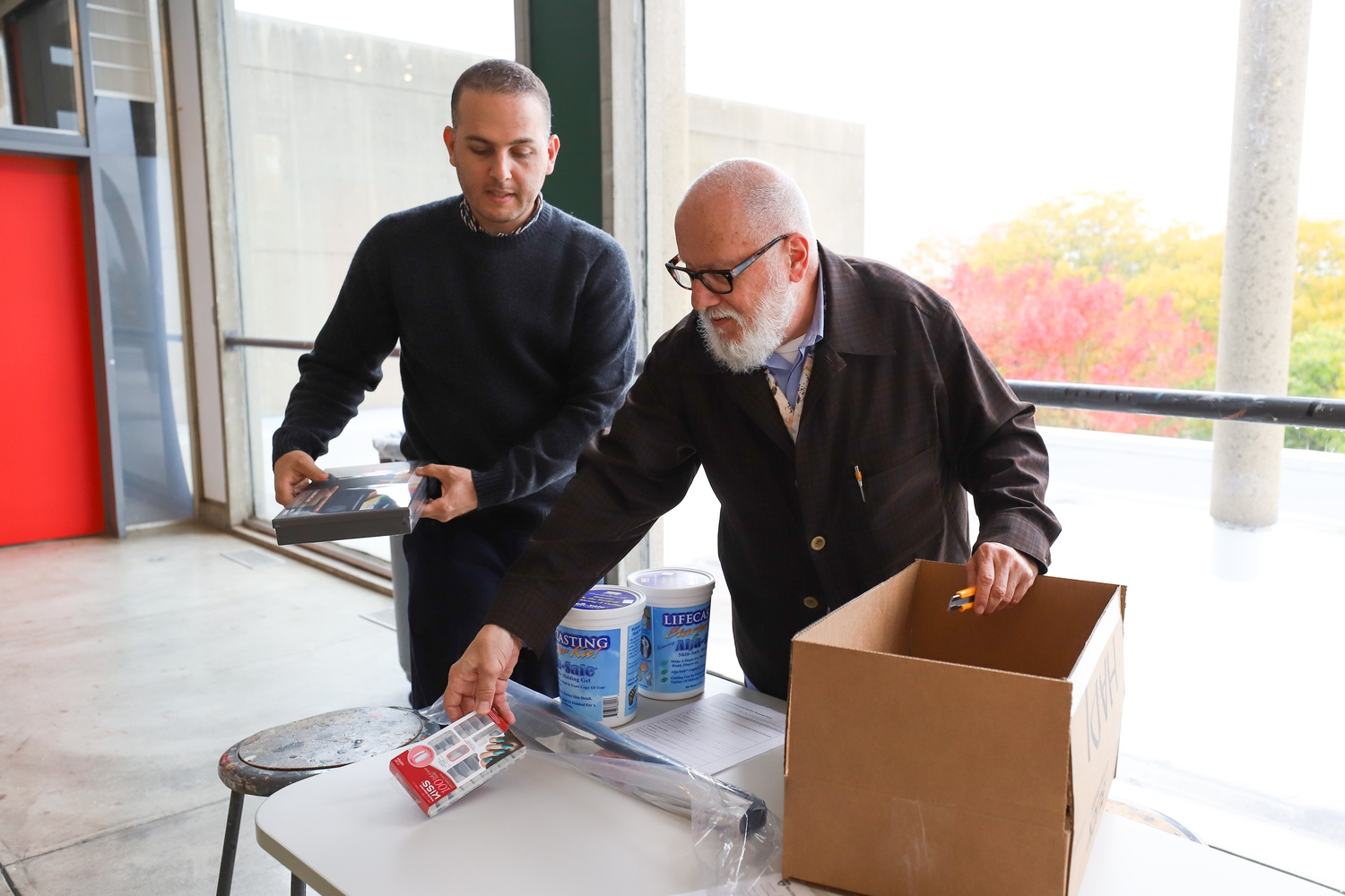 "Professor and artist Stephen J. Prina and teaching fellow Hadi Fallahpisheh unpack a student's project materials for their class Art, Film, and Visual Studies 80: ""Loitering: Studio Course."""