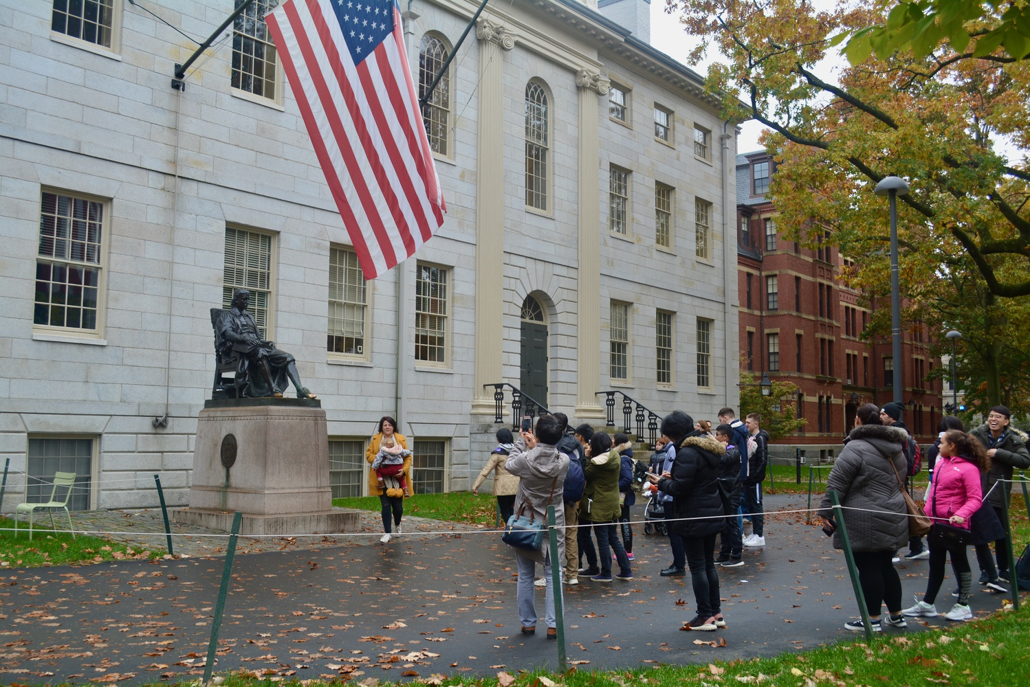 Tourists take photos of the John Harvard statue in front of University Hall.