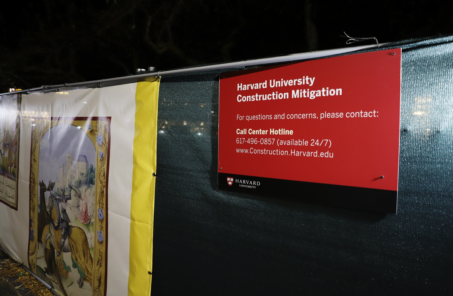 A construction mitigation sign hangs on a fence outside the Houghton Library construction site in Harvard Yard.