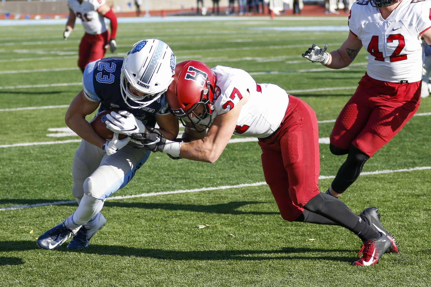 Harvard safety Cole Thompson attempts a late-in-the-game takedown of a Lions running back.