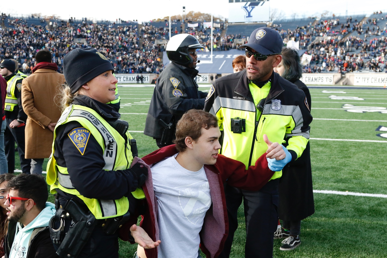 Police officers confront Harvard protester Andrés de Loera-Brust '20 on the field of the Yale Bowl. Divest protesters from both Harvard and Yale stormed the field during halftime of the 136th edition of the Game.