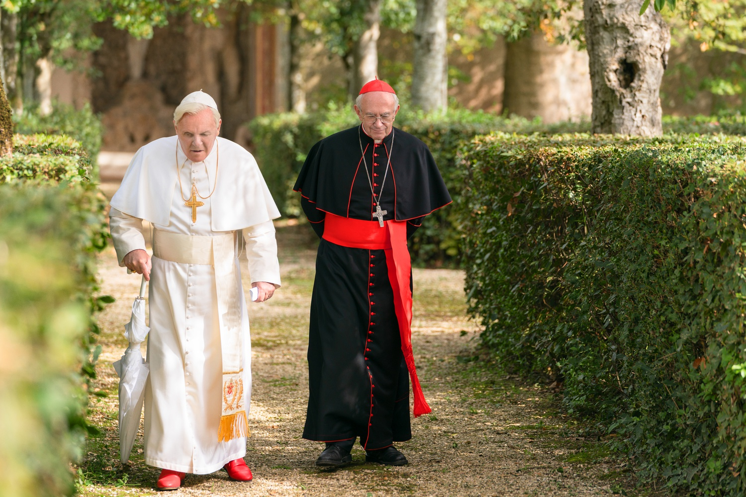 """Anthony Hopkins (left) plays Pope Benedict and Jonathan Pryce (right) plays Pope Francis in """"The Two Popes"""" (2019), directed by Fernando Meirelles."""