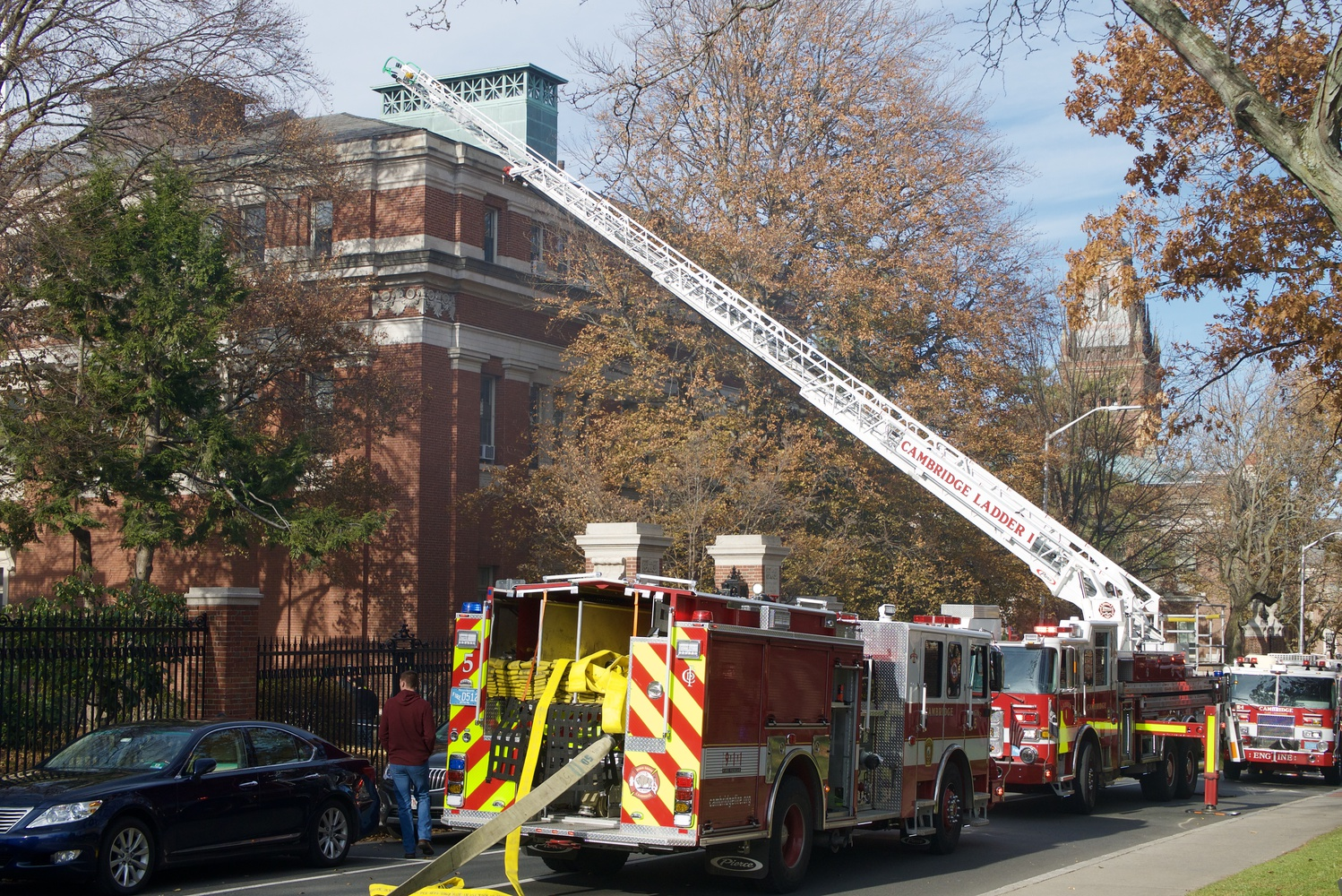 Cambridge firefighters scale the roof of Emerson Hall after smoke started pouring out of the building around noon on Friday.