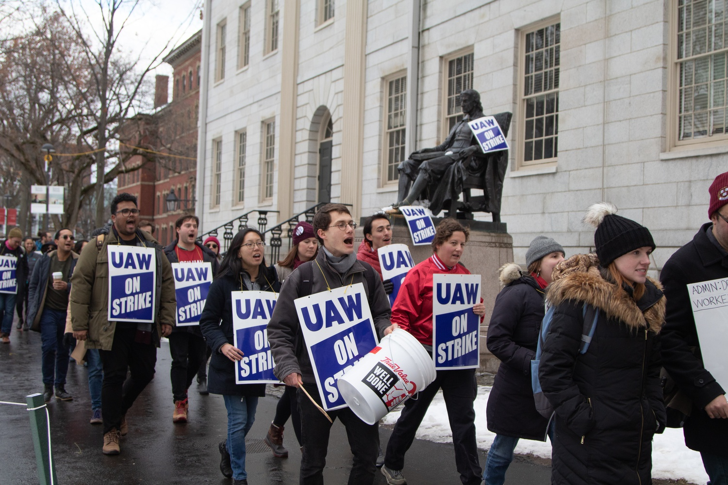 Members of Harvard Graduate Students Union-United Automobile Workers marched past the John Harvard statue bearing buckets and UAW signs.