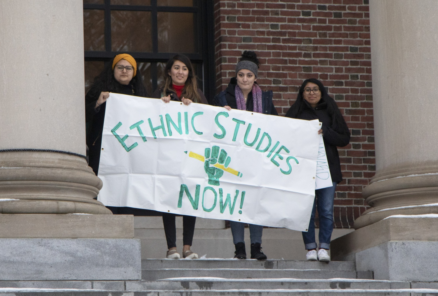 Students hold an Ethnic Studies sign outside Widener Library during a rally on Friday.