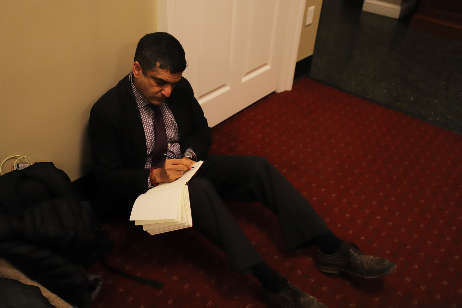 Dean of the College Rakesh Khurana takes notes while watching students occupy the Harvard Office of Admissions and Financial Aid.