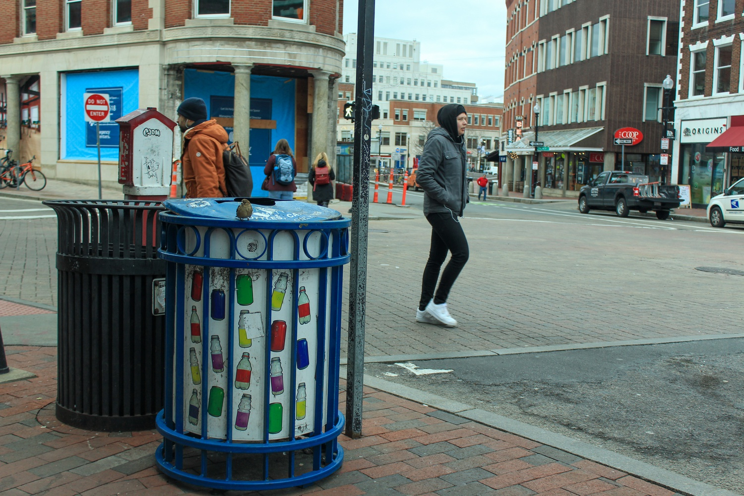 Pedestrians walk by a recycling bin in Harvard Square on Tuesday afternoon.