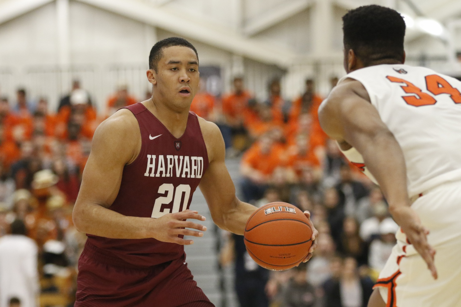 Senior forward Justin Bassey sizes up Princeton center Richmond Aririguzoh. Bassey contributed six points, eight rebounds, and four assists in Harvard's loss.