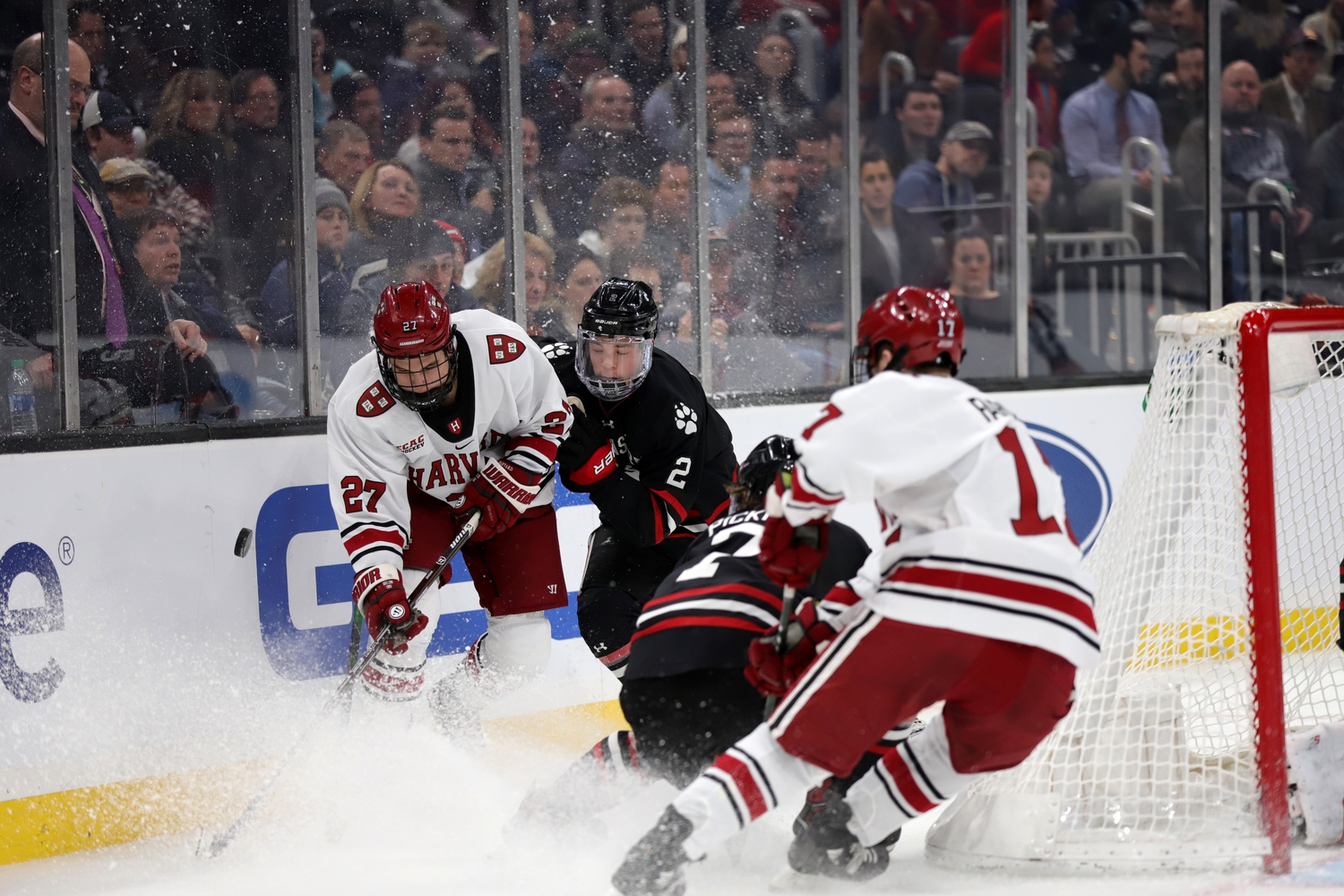 First-year forward Austin Wong of Harvard fights to maintain possession behind the net amid pressure from Huskies sophomore defenseman Jordan Harris.