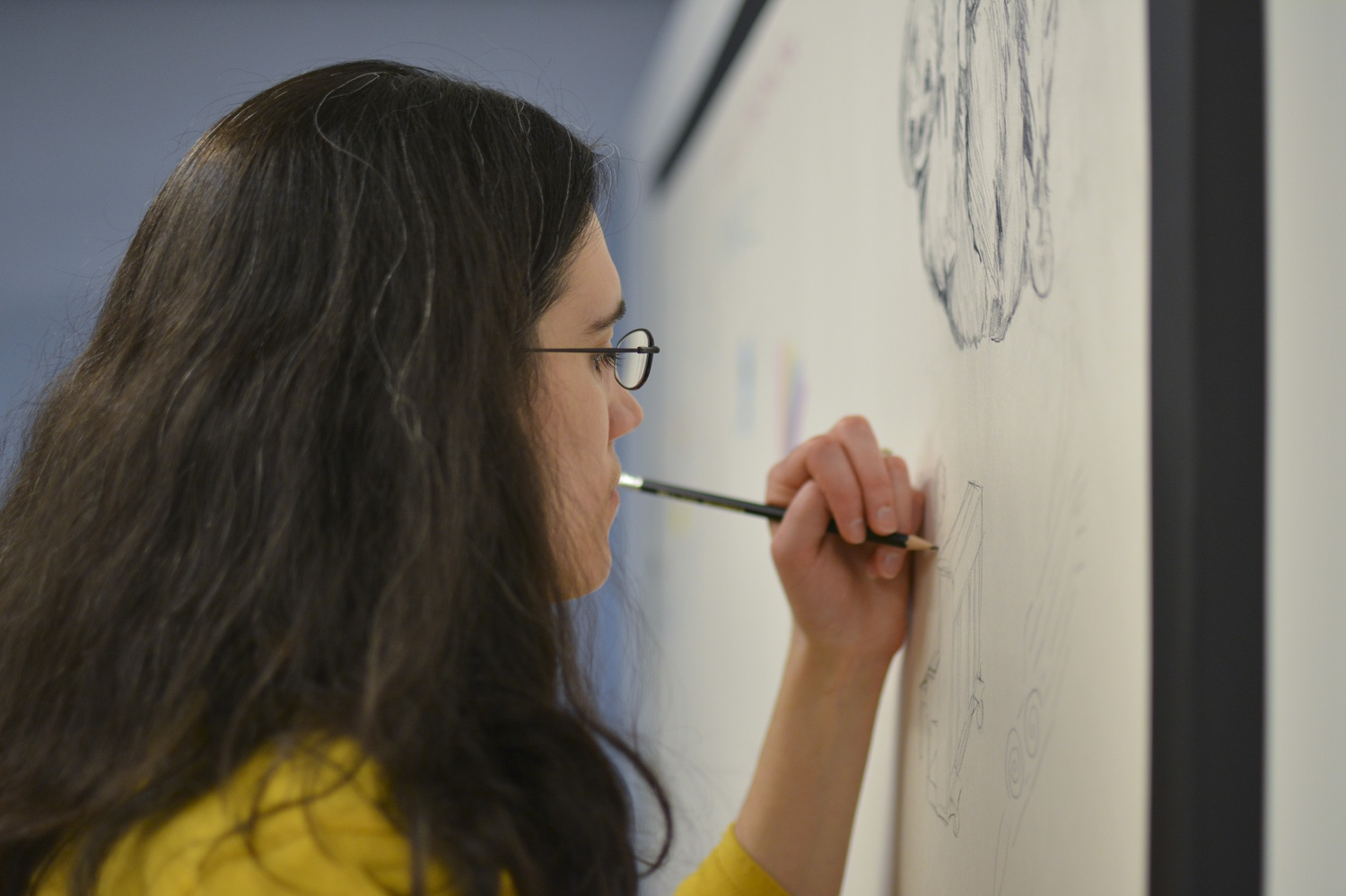 Mia Metivier, program coordinator in the Harvard College Program in General Education, performing live drawing at the Staff Art Show.