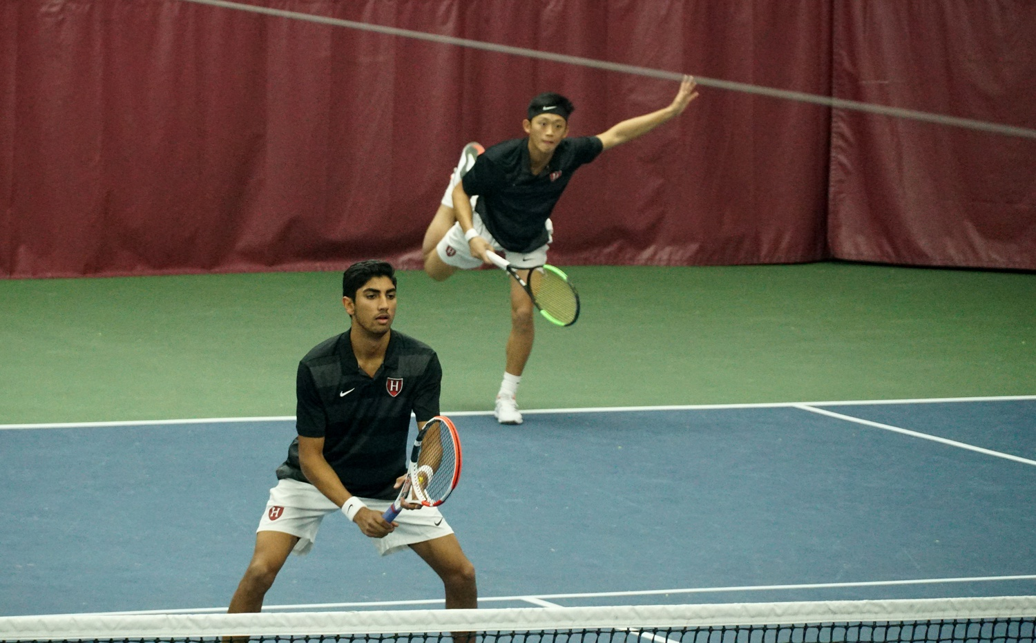 First-year Ronan Jachuk (front) awaits the opponent's return as sophomore Brian Shi (back) delivers a serve in the Harvard victory over Rice. Combined with the women's team, Crimson tennis would go a perfect 3-0 on the weekend.