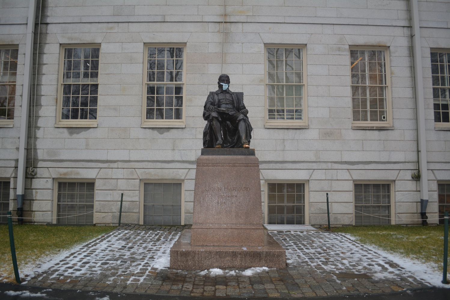 The John Harvard Statue dons a face mask Thursday morning.