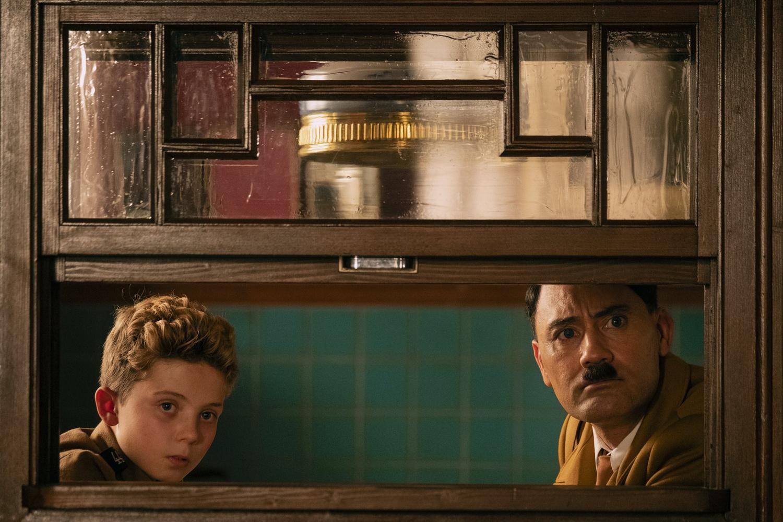"""Roman Griffin Davis (left) stars as Jojo Betzler and Taika Waititi (right) stars as Adolf Hitler in """"Jojo Rabbit"""" (2019), directed by Taika Waititi."""