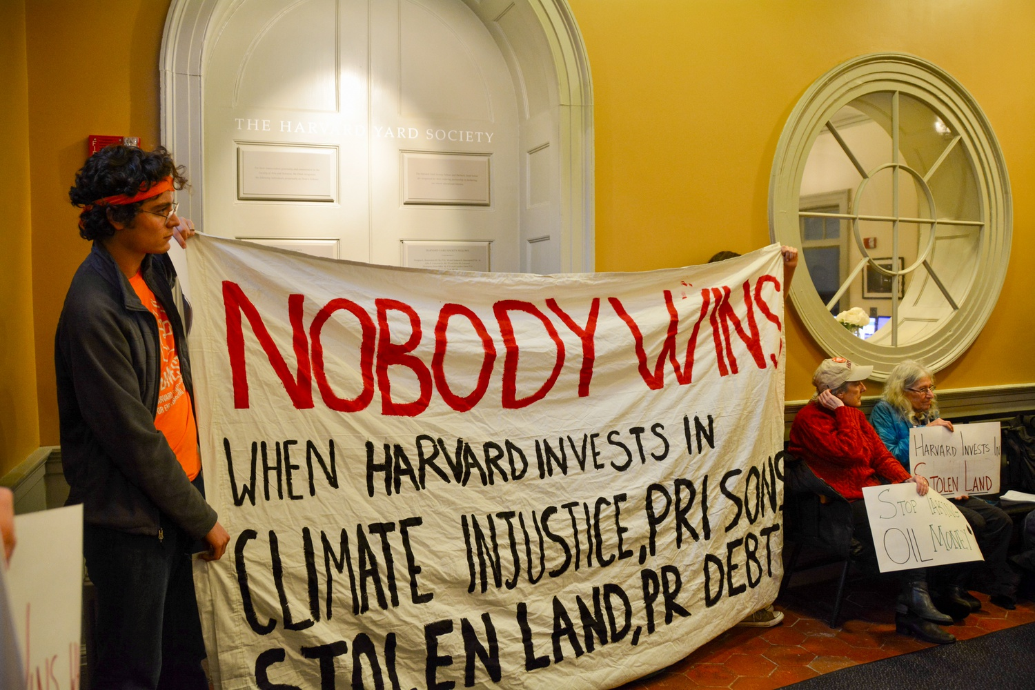 Fossil Fuel Divest Harvard occupies University Hall in February. Alongside faculty and alumni organizations, the student group sent a letter to top administrators calling on Harvard to divest by 2021.