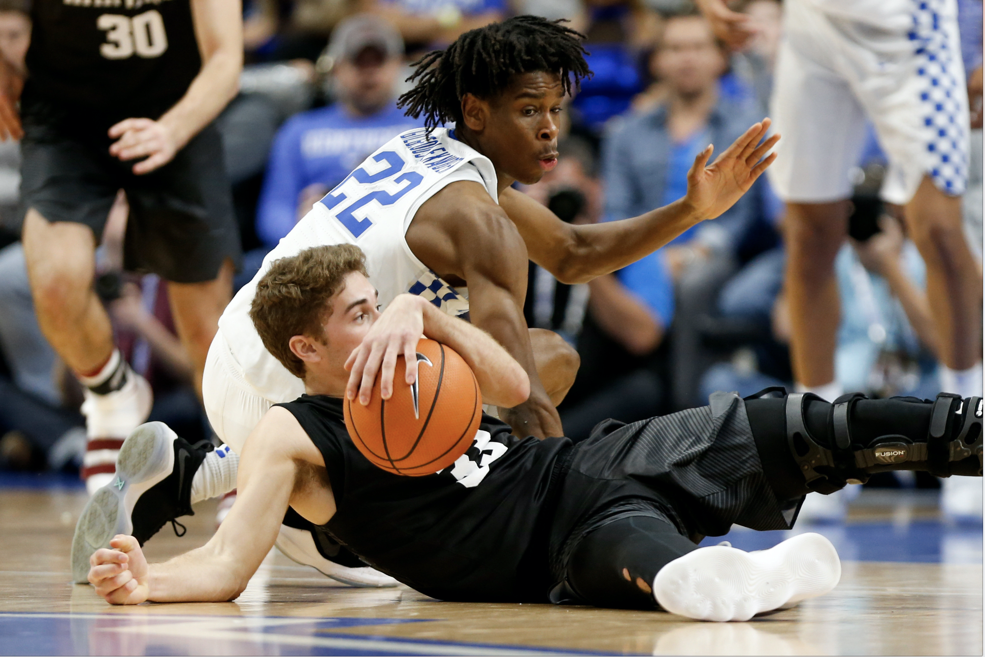 Farley diving to the ground in front of Kentucky's Shai Gilgeous-Alexander, now a member of the Oklahoma City Thunder averaging nearly 20 points per game.