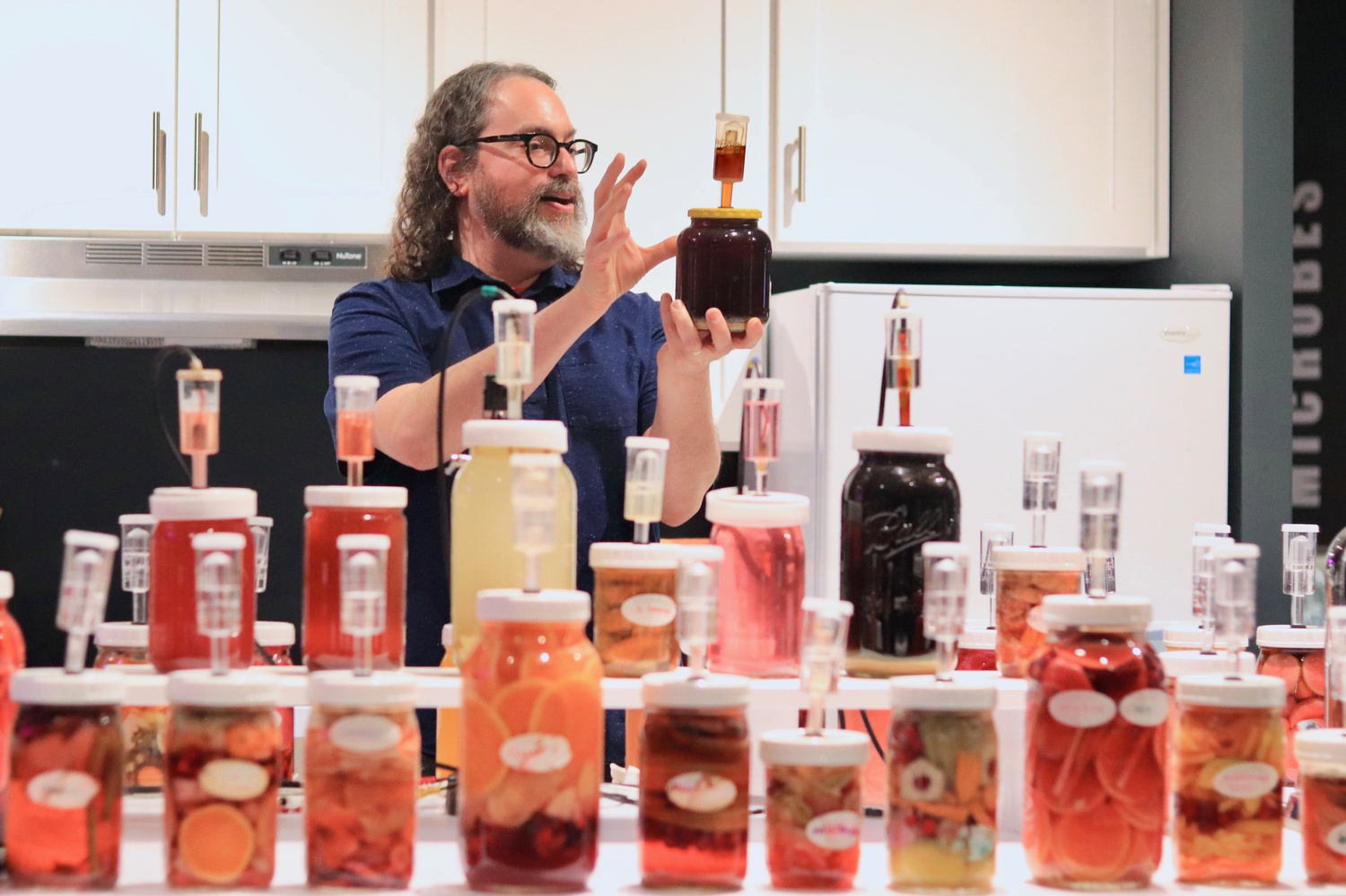 Rosenstock shows the crowd how the microbes in a jar of beer make music as part of his artist talk at the Museum of Natural History.