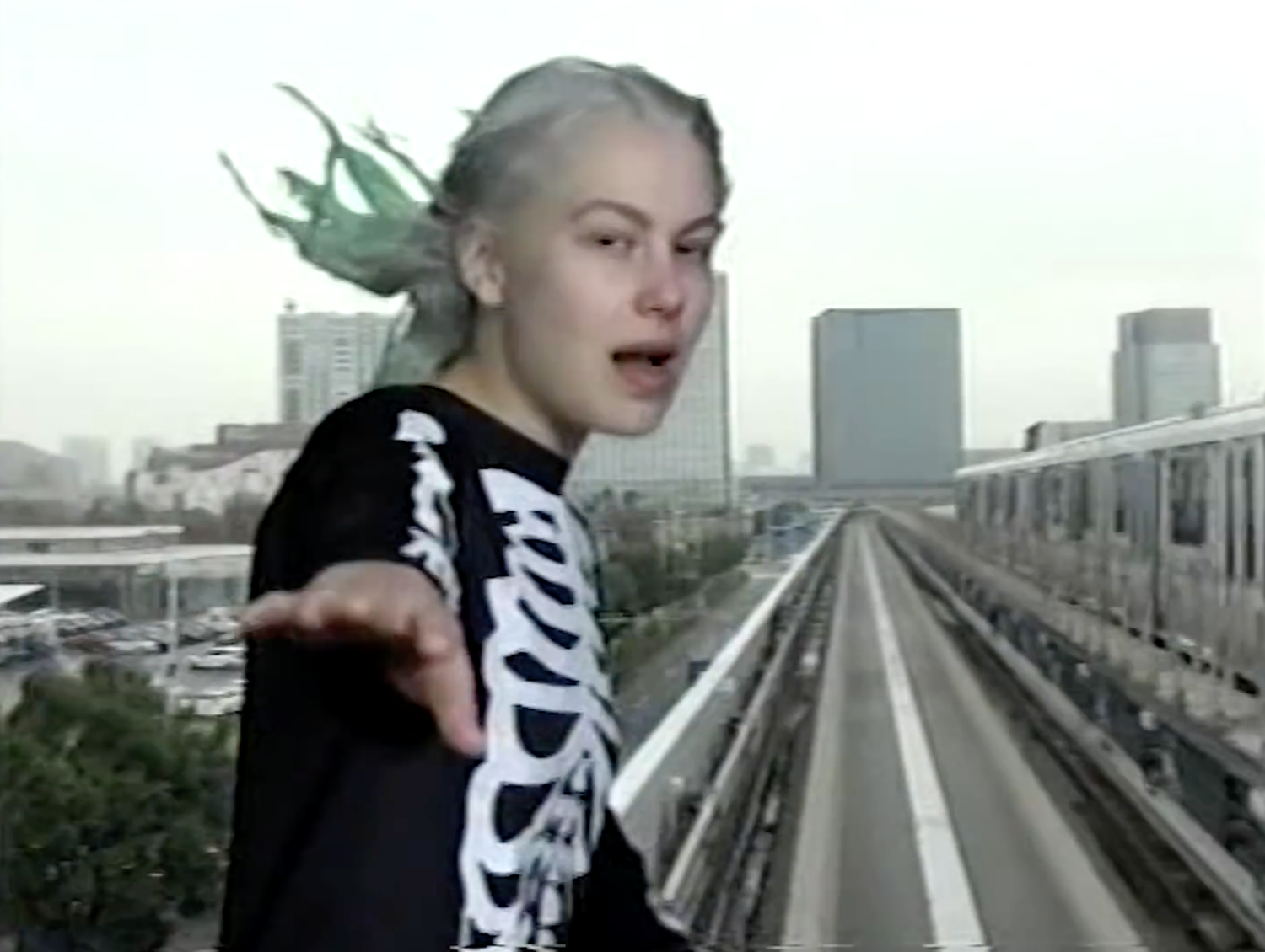 Photograph of Phoebe Bridgers, a white woman in her early twenties with bleached blond hair died vaguely green. She is wearing a black long-sleeved t-shirt with a white skeleton pattern on the front and is standing in front of a greenscreen of a train on the tracks, so that it looks like she is standing on the train and riding it.
