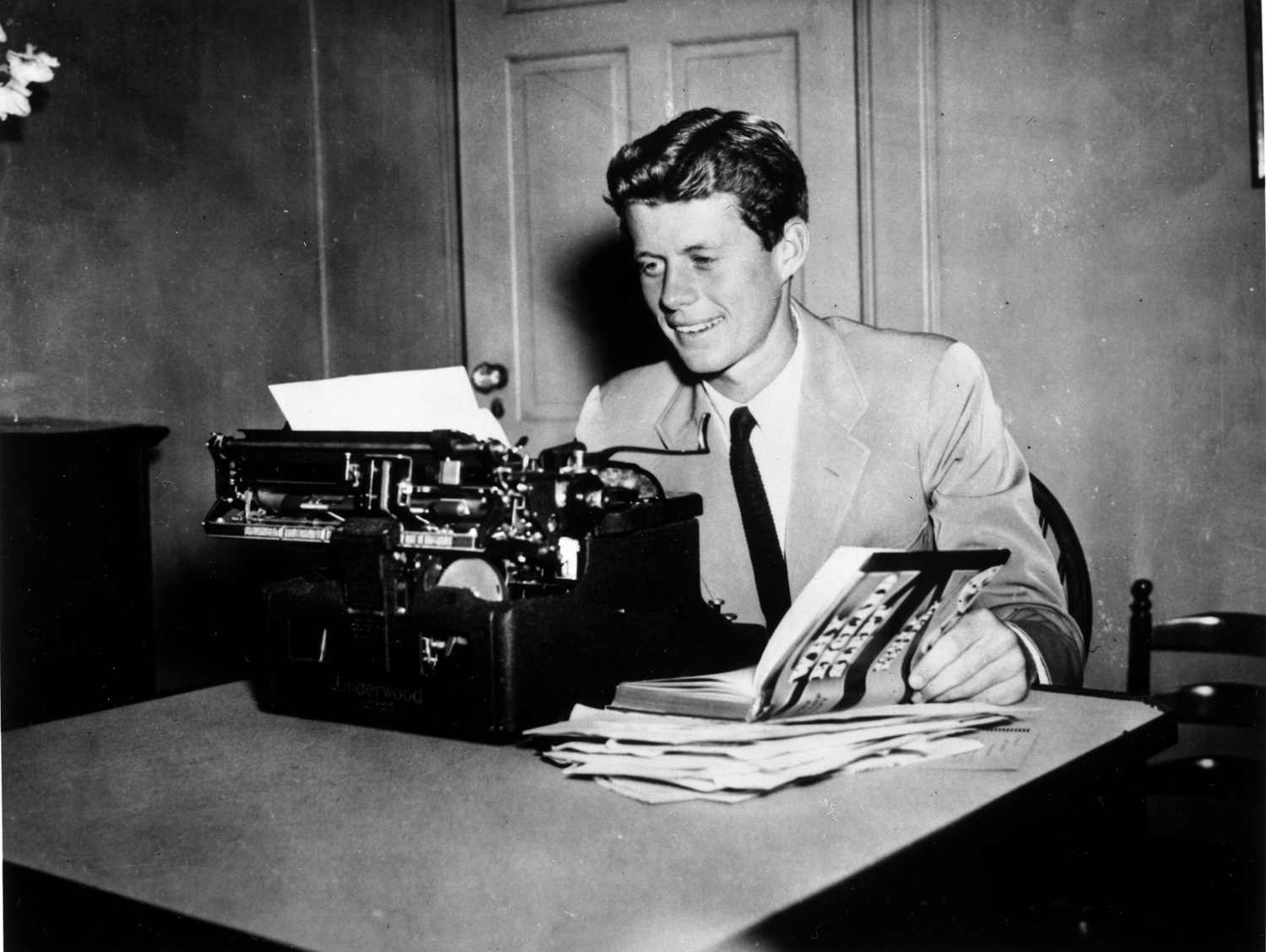 """President John F. Kennedy '40 sits at a typewriter with his book """"Why England Slept,"""" the published version of Kennedy's thesis written in his senior year at Harvard College."""