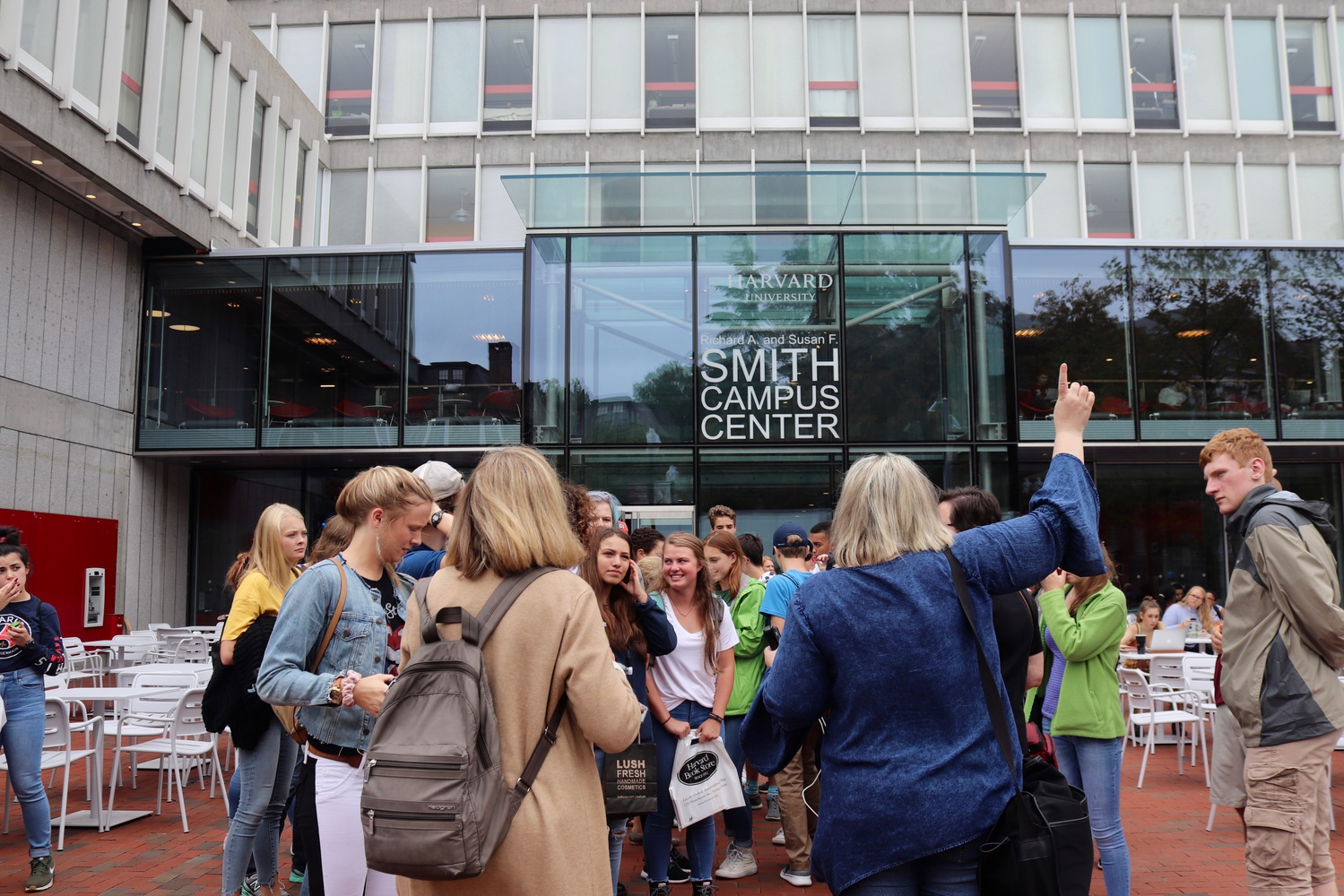 Tourists gather outside the newly renovated Richard A. & Susan F. Smith Campus Center on a warm fall afternoon.